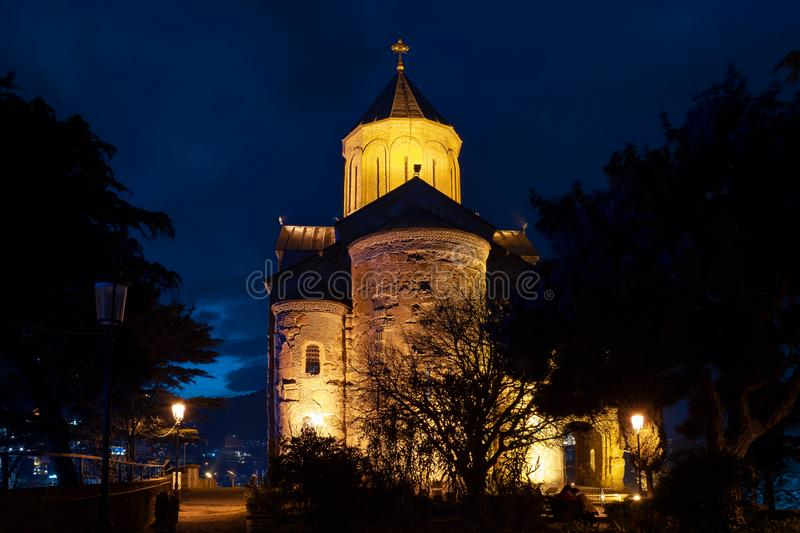 Georgia, Tbilisi - 05.02.2019. - Metekhi church courtyard on top of the hill overlooking Tbilisi old city center - Night scene stock photo
