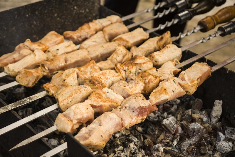 Georgian cuisine. Kebabs. Cooked meat on the coals. Frying meat. Tasty food. Brazier and skewers. Food outdoors. stock images