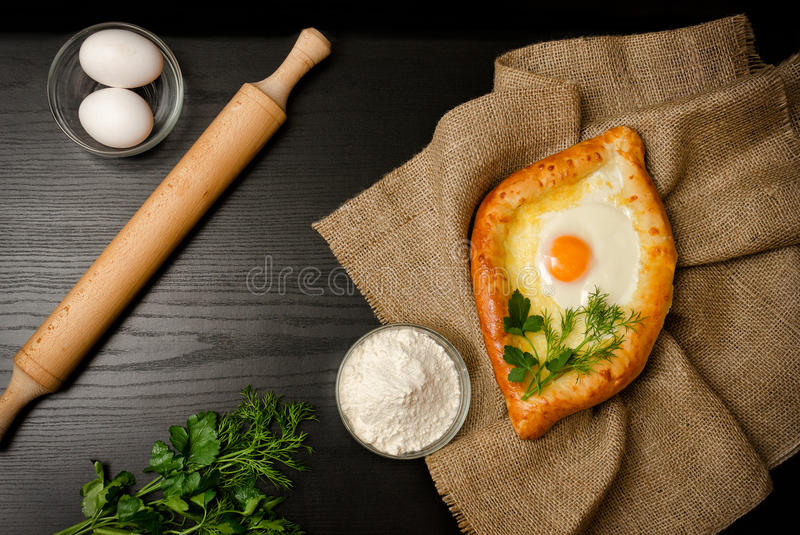 Georgian cuisine. Top view of khachapuri on sackcloth, flour, eggs and rolling pin. Black table. Space for text stock photography