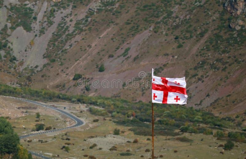 Georgian Flag Waving Against the Valley of Stepantsminda, Khevi province, Georgia. Background royalty free stock image
