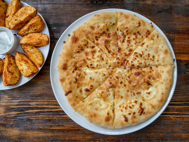 Georgian food Khachapuri and fried potatoes with Mexican sauce on the plate stock image