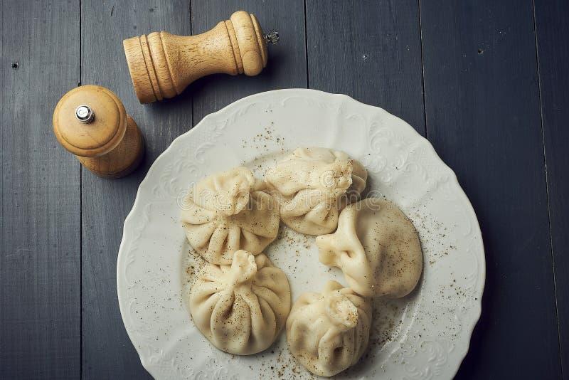 Georgische bollen Khinkali met vlees op witte plaat met exemplaarruimte stock fotografie