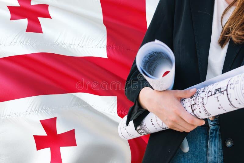 Georgische de holdingsblauwdruk van de Architectenvrouw tegen golvende de vlagachtergrond van Georgië Bouw en architectuurconcept stock fotografie