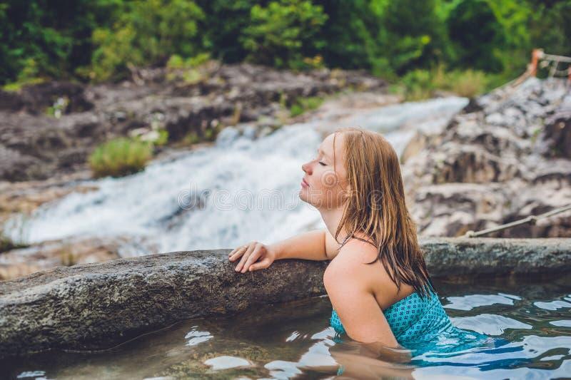 Geotermiczny zdrój Kobieta relaksuje w gorącej wiosny basenie przeciw tłu siklawa zdjęcie stock