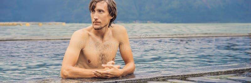 Geotermiska Spa man som kopplar av i p?l f?r varm v?r Ung man som tycker om att bada som kopplas av i en lagun för blått vatten,  royaltyfri bild