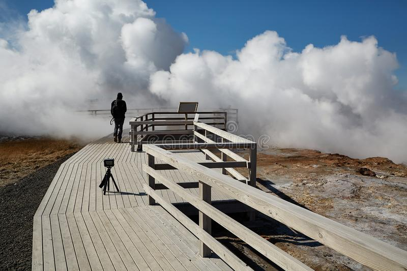 Geothermal Activity in Iceland. Geothermal hot springs at Gunnuhver, videographer filming himself walking into the mist royalty free stock photography