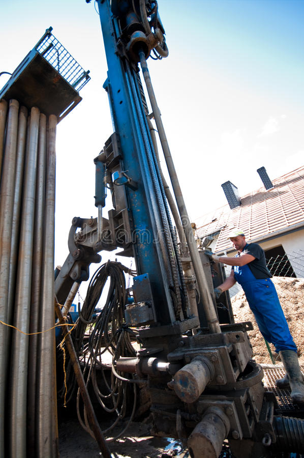 Geothermal drilling machine. In action with worker operating it. Source for renewable energy for a private house stock photography