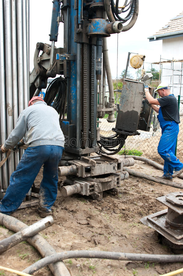 Geothermal drilling machine. Two middle aged workman using modern geothermal drilling machine with house in background stock images