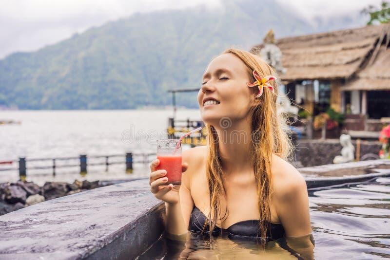 Geothermal Spa Χαλάρωση γυναικών στην καυτή λίμνη άνοιξη ενάντια στη λίμνη καυτή έννοια ελατηρίων Πίνοντας χυμός γκοϋαβών στοκ εικόνες