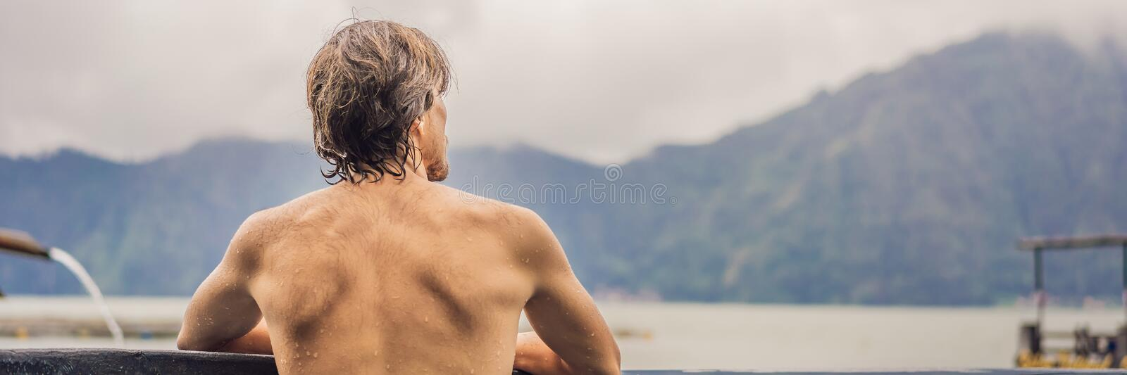 Geothermal spa. Man relaxing in hot spring pool. Young man enjoying bathing relaxed in a blue water lagoon, tourist royalty free stock images