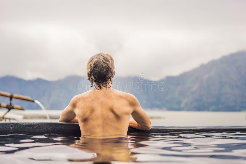 Geothermal Spa mens het ontspannen in hete de lentepool Jonge mens die van baden genieten ontspannen in een blauwe waterlagune, t royalty-vrije stock foto