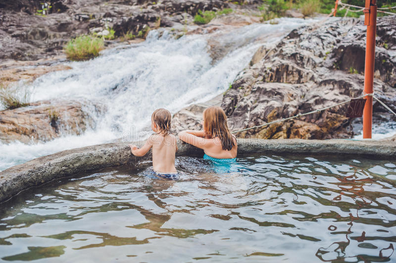 Geothermal spa. Mother and son relaxing in hot spring pool against the background of a waterfall stock photography