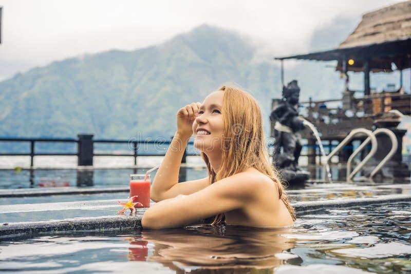 Geothermal Spa Vrouw het ontspannen in hete de lentepool tegen het meer heet de lentesconcept Drinkend guavesap stock foto