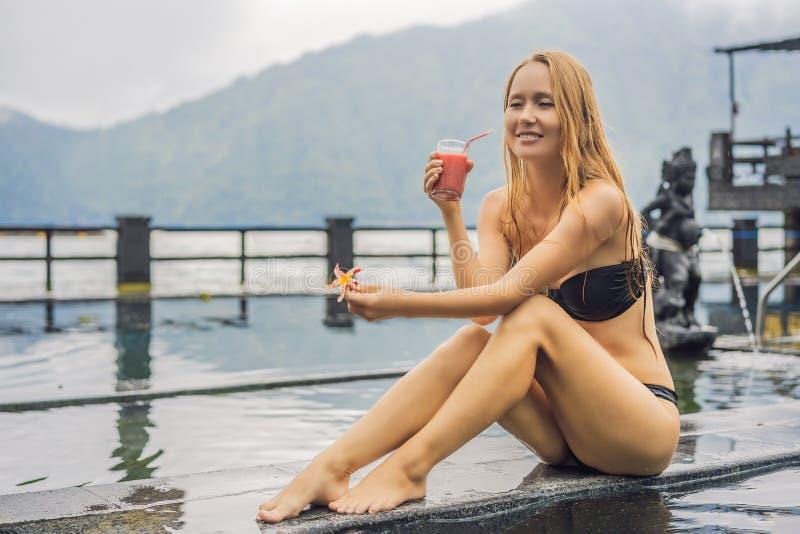 Geothermal Spa Vrouw het ontspannen in hete de lentepool tegen het meer heet de lentesconcept Drinkend guavesap royalty-vrije stock fotografie