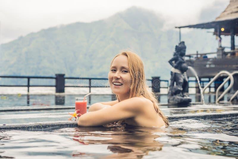 Geothermal Spa Vrouw het ontspannen in hete de lentepool tegen het meer heet de lentesconcept Drinkend guavesap stock foto's