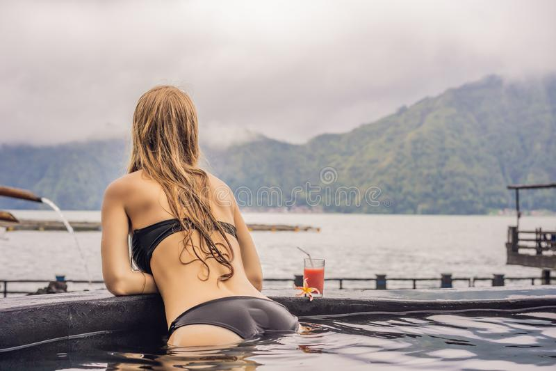 Geothermal spa. Woman relaxing in hot spring pool against the lake. hot springs concept royalty free stock photo