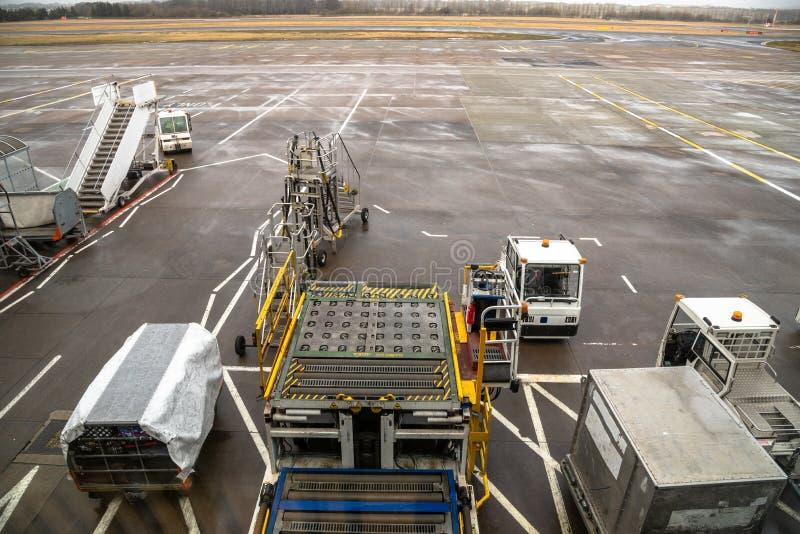 Gepäck-Wagen und andere Handhabungsgeräte auf dem Asphalt eines Flughafens stockbilder