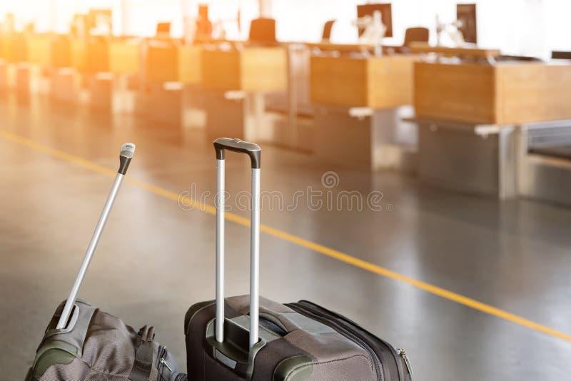 Gepäckkoffer am Flughafenabfertigungsgebäude mit leerem Abflugschalter stockfoto