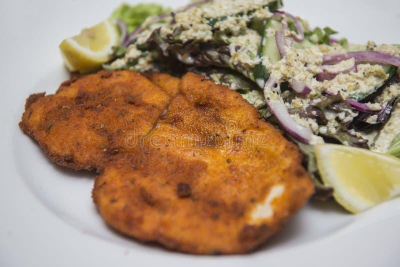 Gepaneerde kippenborst met plantaardige salade stock foto