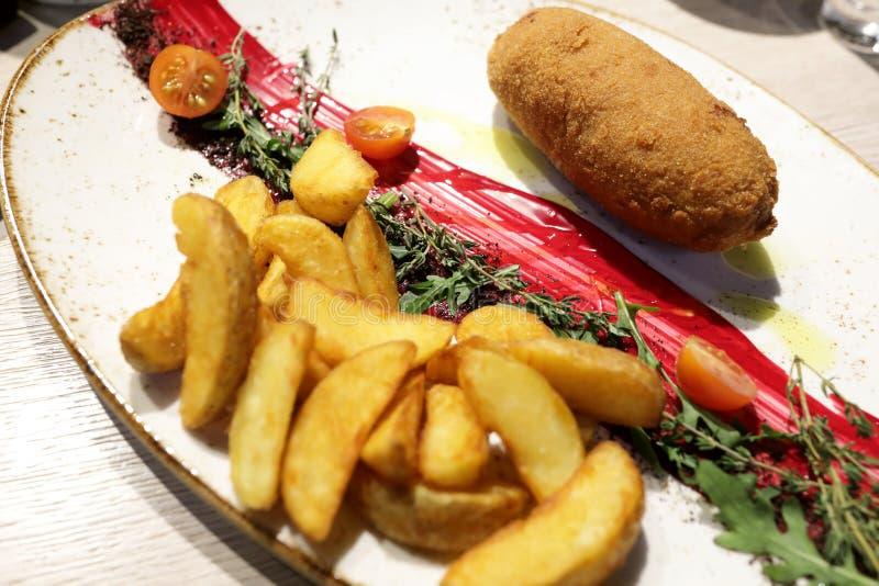 Gepaneerde kotelet met aardappels stock afbeeldingen