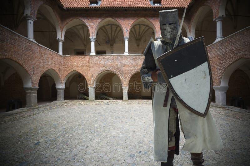 Gepantserde ridder op binnenplaats van middeleeuws kasteel royalty-vrije stock afbeelding