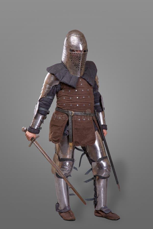 Gepanzerter Ritter in einem Sturzhelm und mit einer Klinge über grauem Hintergrund lizenzfreie stockfotografie