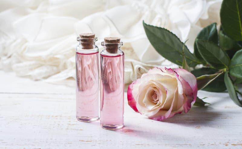 Geparfumeerd rozewater in een fles op een houten lijst royalty-vrije stock foto's