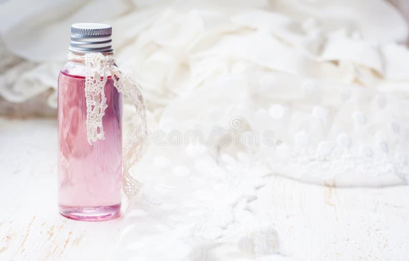 Geparfumeerd rozewater in een fles op een houten lijst Selectieve FO stock afbeeldingen