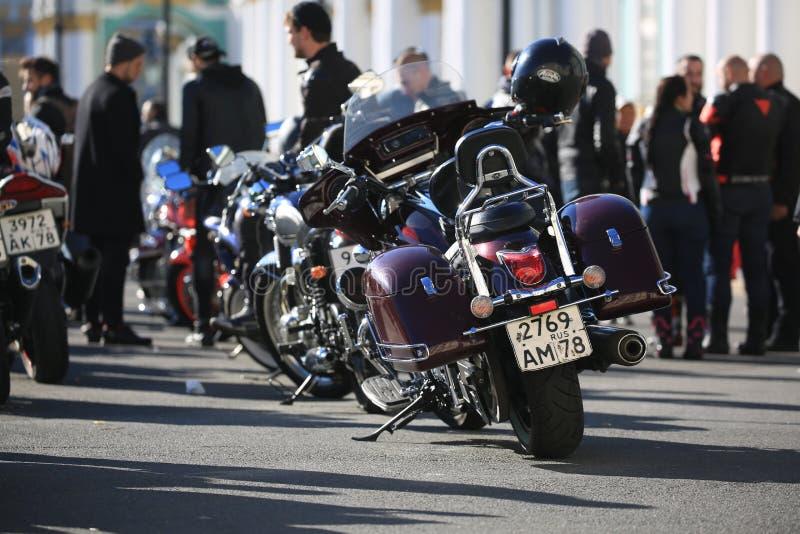 Geparkeerde motorfietsen en mensen in zonnige dag stock fotografie