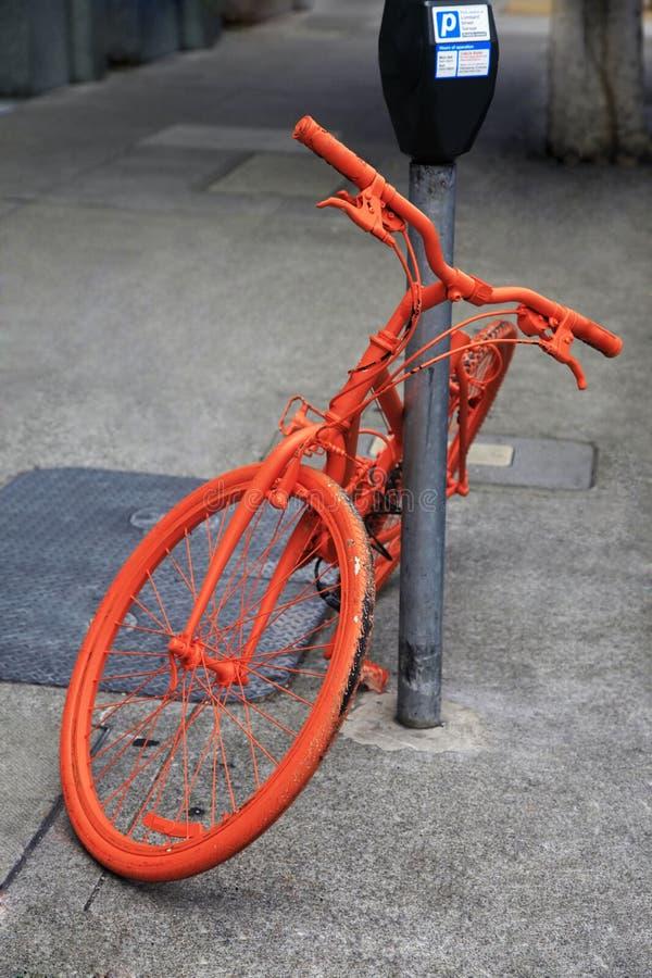 Geparkeerde oranje fiets royalty-vrije stock fotografie