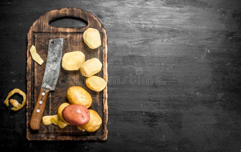 Gepelde aardappels met een mes op een oude scherpe raad royalty-vrije stock afbeelding