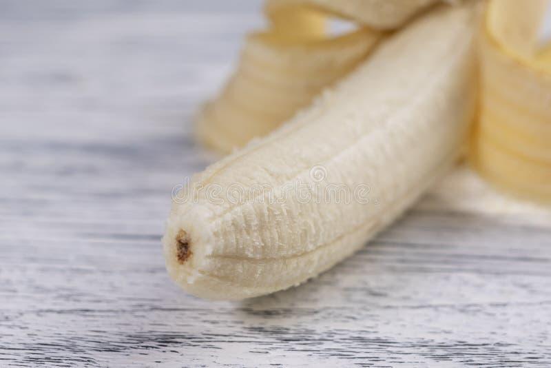 Gepelde banaanschil op een lichte houten lijst stock foto