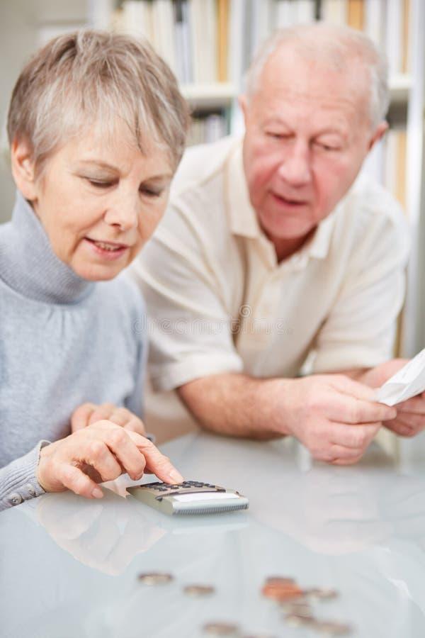 Gepensioneerde en gepensioneerdepaar die boekhouding doen stock afbeeldingen