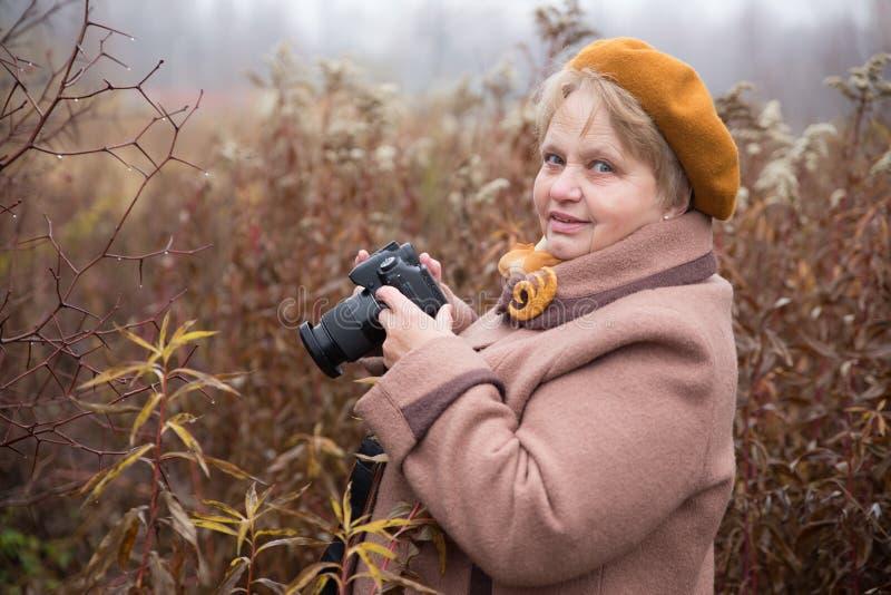 Gepensioneerdevrouw met camera openlucht stock afbeeldingen