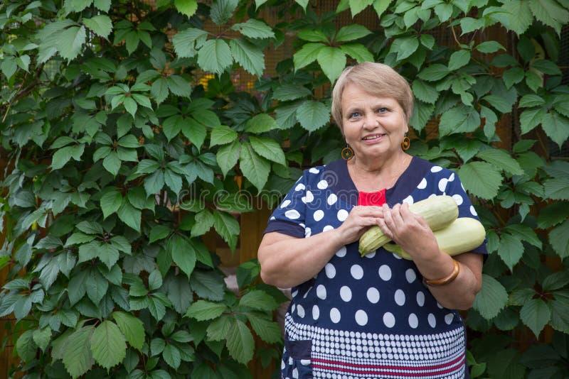 Gepensioneerdevrouw met pompoen in tuin stock foto's