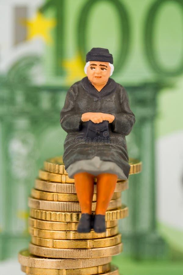 Gepensioneerdezitting op stapel van geld royalty-vrije stock afbeelding
