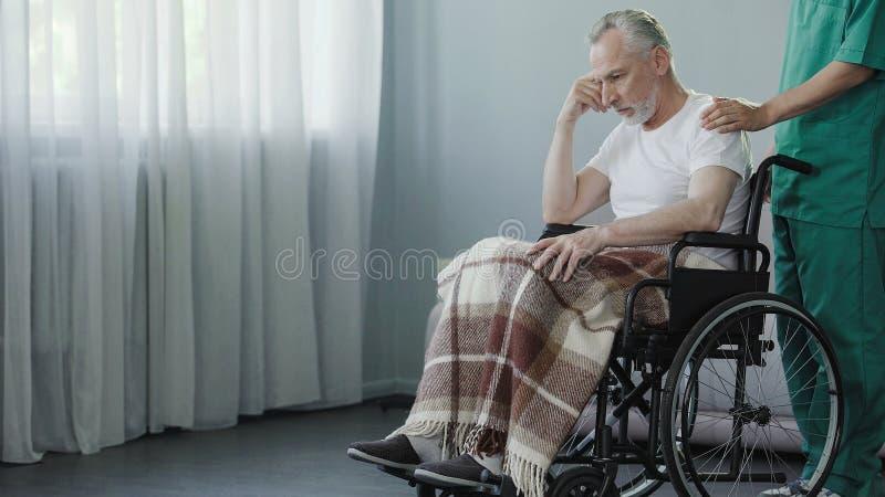 Gepensioneerdezitting in rolstoel, verpleger ondersteunend oude patiënt bij kliniek royalty-vrije stock foto's
