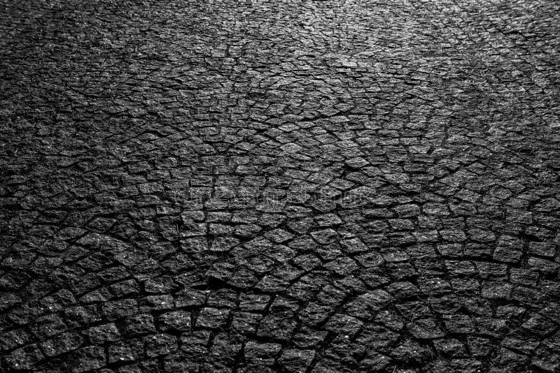 Gepflasterte Stadt mit Porphyrwürfeln Beschaffenheit des Kopfsteins Boden einer Straße mit Steinfliesen lizenzfreie stockfotos