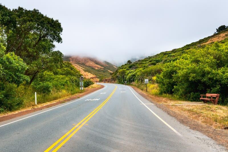 Gepflasterte Straße mit einer 35 MPH-Höchstgeschwindigkeit, die Marin Headlands durchläuft; bewölkter und nebeliger Tag; Marin Co stockbild