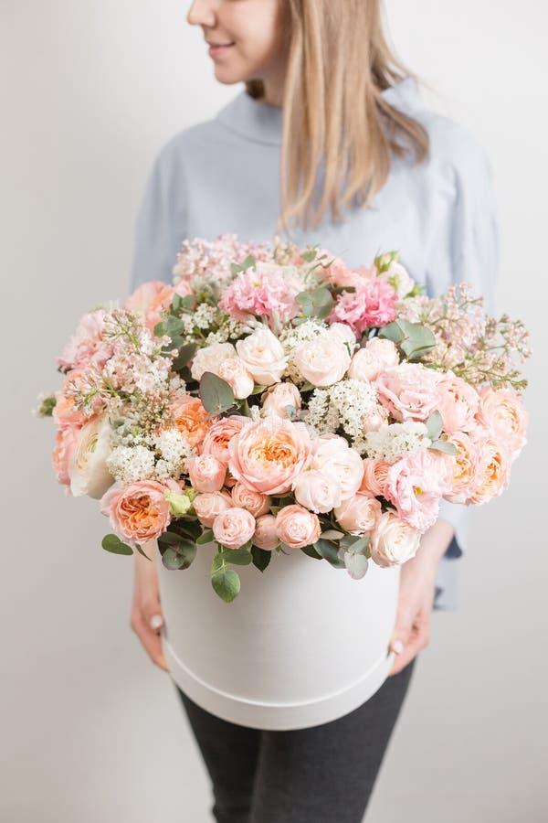 Geplaatste bloemen mooi luxeboeket in vrouwenhand het werk van de bloemist bij een bloemwinkel Witte ronde doos royalty-vrije stock afbeelding