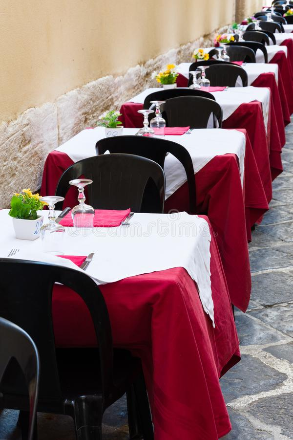 Geplaatste lijsten en lege die stoelen in een restaurant in Ortigia worden opgesteld, stock foto's