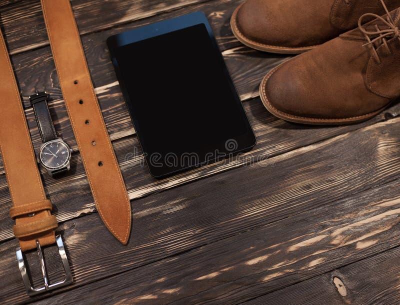 Geplaatste mensen` s bruine kleding en toebehoren: laarzen, leerriem, horloge PC-tablet royalty-vrije stock afbeeldingen