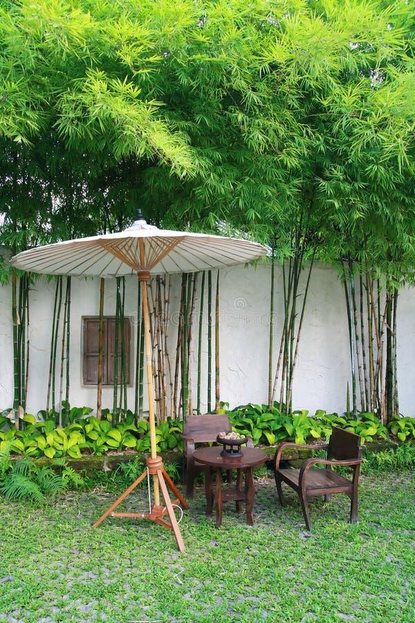 Geplaatste stoel en paraplu in tuin stock afbeelding