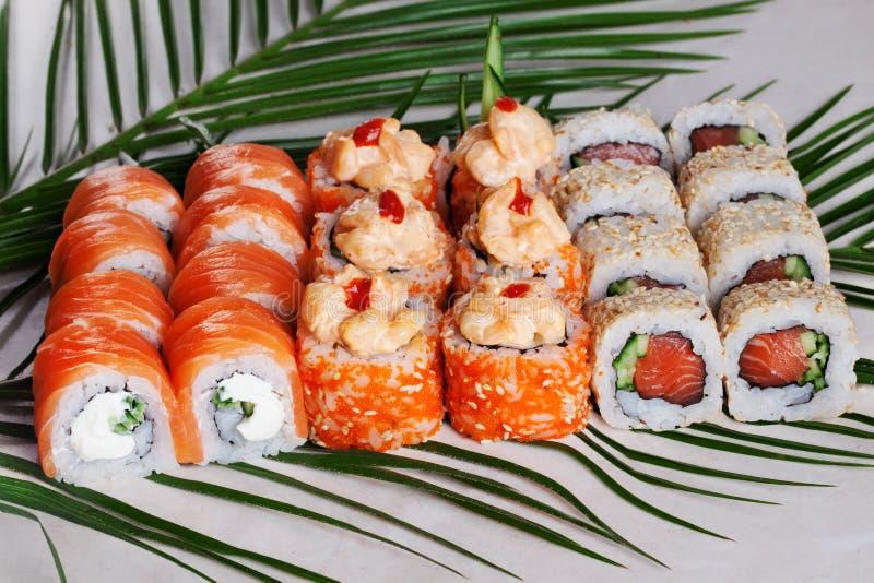 Geplaatste sushi de broodjes, smakelijk, groot, Philadelphia, zalm, hete masago, oranje, saus, kimchi, sesam, rookten, tropische  stock foto's
