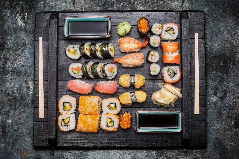 Geplaatste sushi: maki, nigiri, ousidebroodjes met sojasaus worden gediend, legde gember en wasabi op donkere houten plaat die in stock foto
