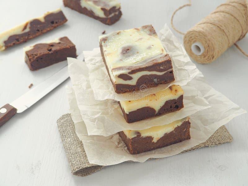 Geplakt van chocolade brownies op perkament Verpakkingsproces Marmeren chocoladekaastaart Selectieve nadruk op de voorzijde stock afbeeldingen