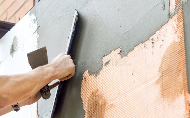 Gepleisterde muren met een spatel stock foto's
