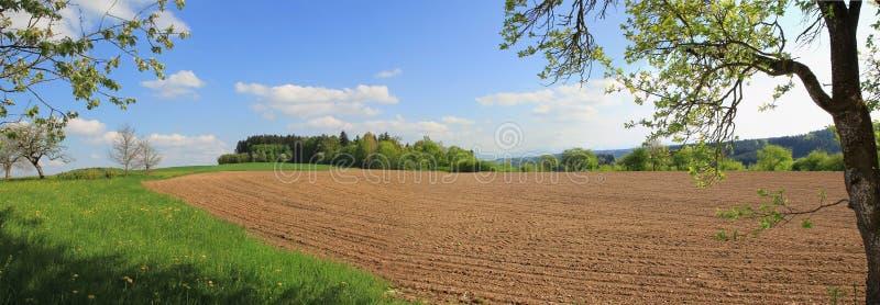Geploegde landbouwgrond bij de lente, landbouwlandschap stock afbeeldingen