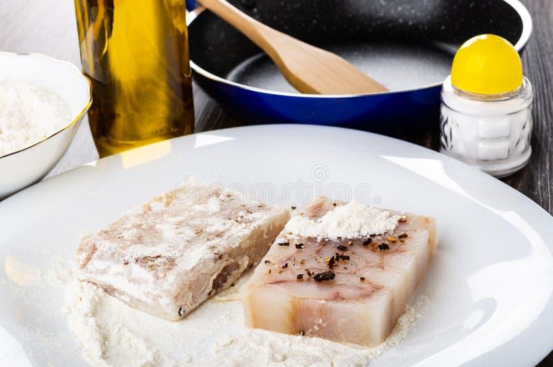Gepresste Stücke der Pollockleiste im Mehl mit Würze auf Teller, Flasche Pflanzenöl, Bratpfanne, Salz auf Holztisch stockfoto