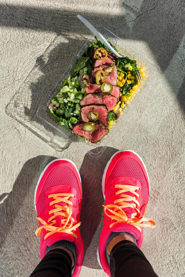 Gepropageerde maaltijdfitnessvrouw met gym foot stock afbeelding
